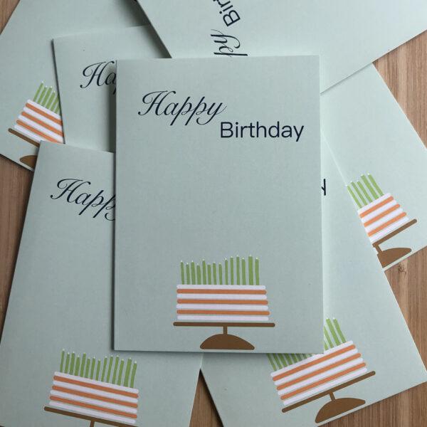 Wenskaart happy birthday cake, blauwe kaart met oranje wit gestreepte taart met groene kaarsjes, op een stapel met dezelfde kaarten.