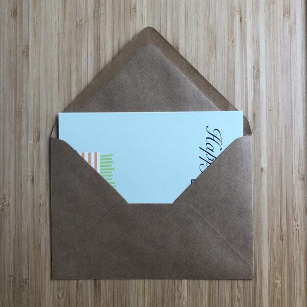 Wenskaart happy birthday cake, blauwe kaart met oranje wit gestreepte taart met groene kaarsjes, half in een kraft envelop.