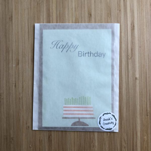 Wenskaart happy birthday cake, blauwe kaart met oranje wit gestreepte taart met groene kaarsjes, verpakt in een pergamijn zakje.