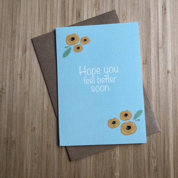 Wenskaart beterschap gele bloemen. Blauwe kaart met gele bloemen. Met een kraft envelop