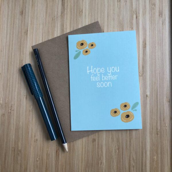 Wenskaart beterschap gele bloemen. Blauwe kaart met gele bloemen. Met een kraft envelop en pen en potlood.