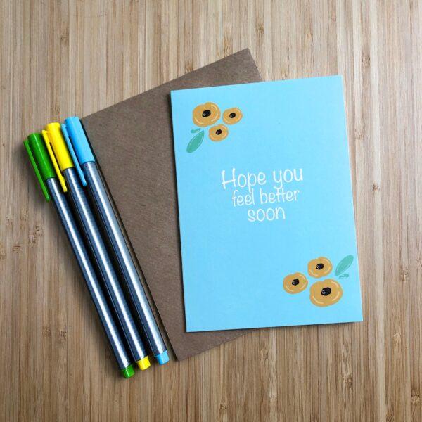 Wenskaart beterschap gele bloemen. Blauwe kaart met gele bloemen. Met een kraft envelop en gekleurde pennen.