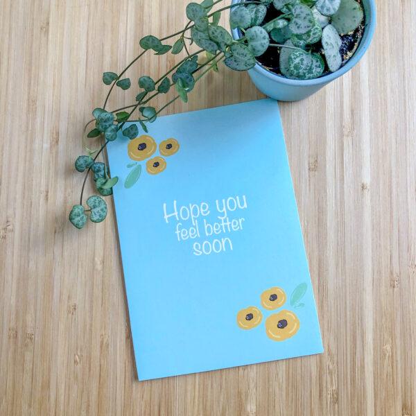Wenskaart beterschap gele bloemen. Blauwe kaart met gele bloemen. Met een plantje.