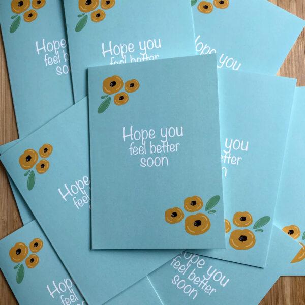 Wenskaart beterschap gele bloemen. Blauwe kaart met gele bloemen, op een stapel met dezelfde kaarten.