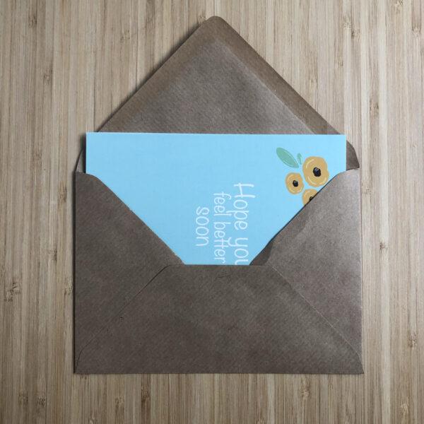 Wenskaart beterschap gele bloemen. Blauwe kaart met gele bloemen, half in een kraft envelop.