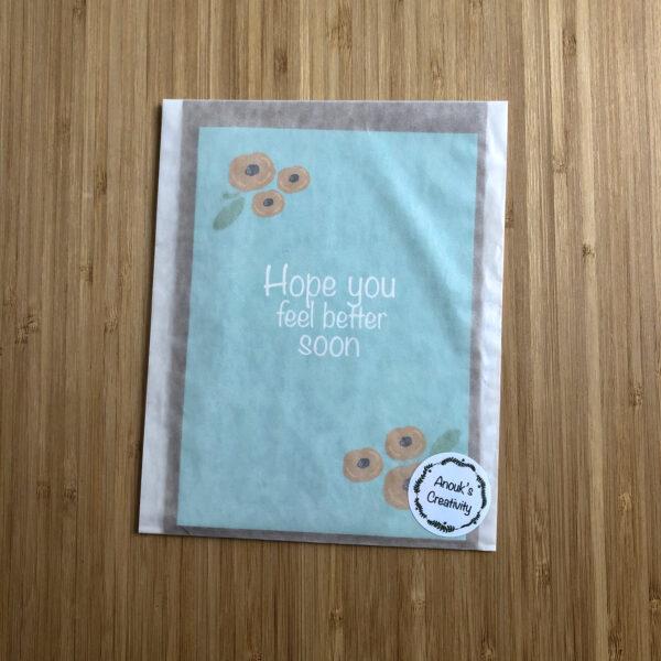Wenskaart beterschap gele bloemen. Blauwe kaart met gele bloemen, verpakt in een pergamijn zakje.
