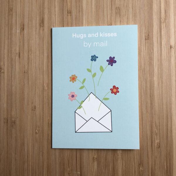 Wenskaart hugs and kisses by mail. Blauwe kaart met envelop erop met bloemen.