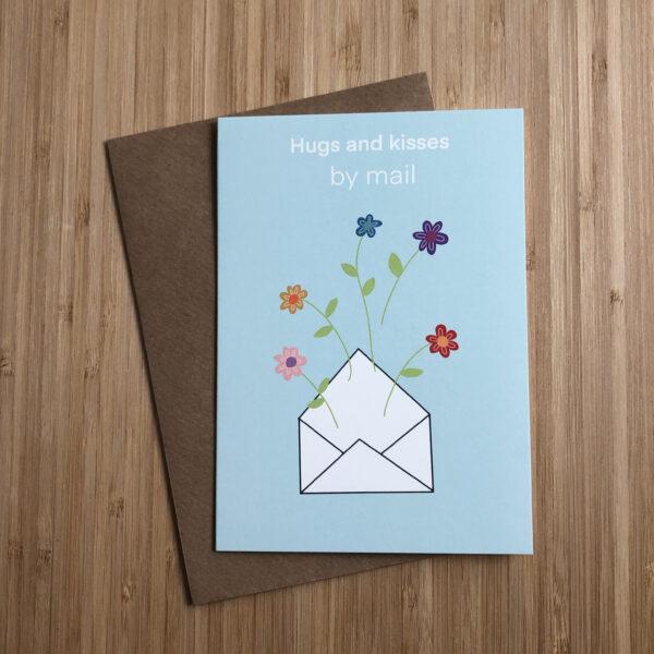 Wenskaart hugs and kisses by mail. Blauwe kaart met envelop erop met bloemen. Met een kraft envelop.