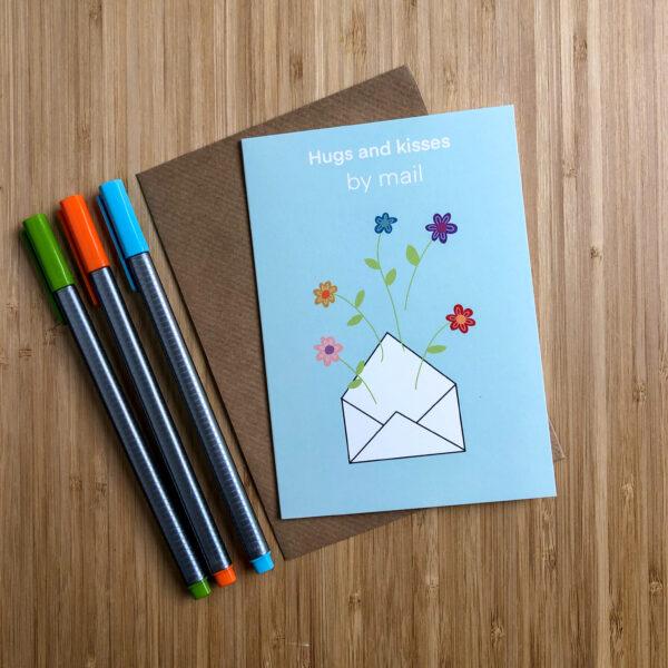 Wenskaart hugs and kisses by mail. Blauwe kaart met envelop erop met bloemen. Met een kraft envelop en gekleurde pennen.