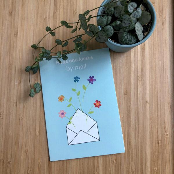 Wenskaart hugs and kisses by mail. Blauwe kaart met envelop erop met bloemen. Met een plantje.