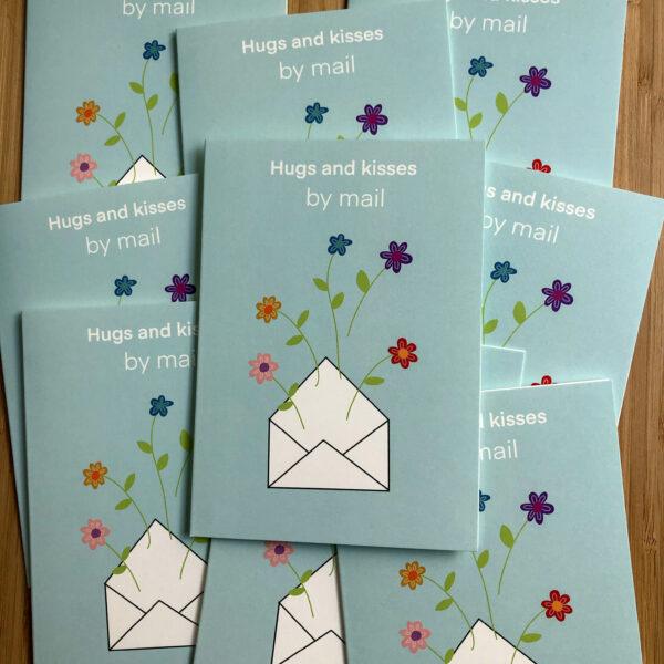 Wenskaart hugs and kisses by mail. Blauwe kaart met envelop erop met bloemen. Op een stapel met dezelfde kaarten.