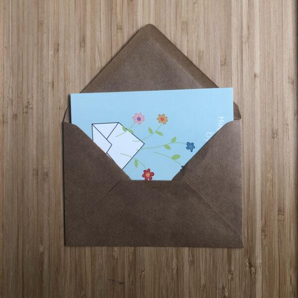 Wenskaart hugs and kisses by mail. Blauwe kaart met envelop erop met bloemen. De kaart is half in een kraft envelop gestoken.