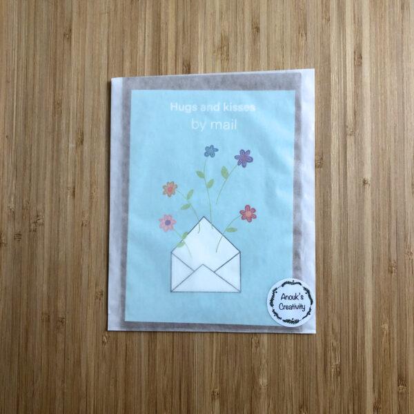 Wenskaart hugs and kisses by mail. Blauwe kaart met envelop erop met bloemen. Verpakt in een pergamijn zakje.