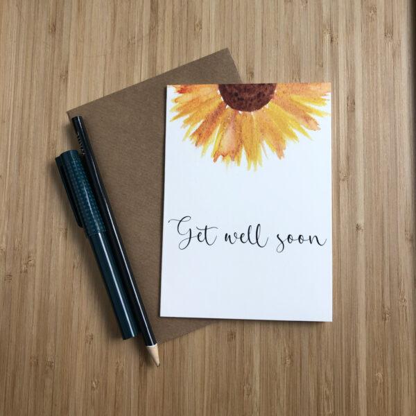 Wenskaart get well soon zonnebloem met een kraft envelop en pen en potlood.