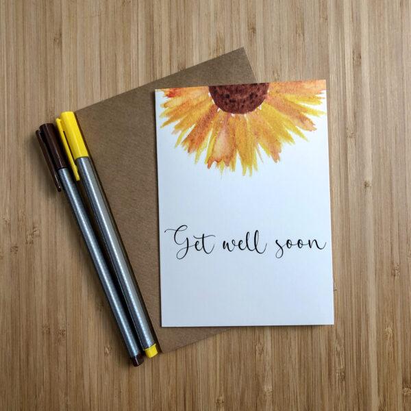 Wenskaart get well soon zonnebloem met een kraft envelop en gekleurde pennen.