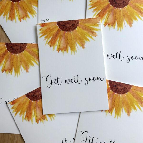 Wenskaart get well soon zonnebloem, op een stapel met dezelfde kaarten.